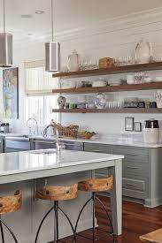 again the natural wood of these shelves looks beautiful against a white backdrop of subway tile in this white shaker farmhouse kitchen via dougelissa