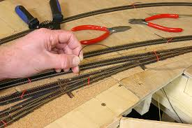 track nigel s mountains and modelling page  this picture shows the feeding of bell wire for droppers through holes in the baseboard top at the west end of the reception yard roads