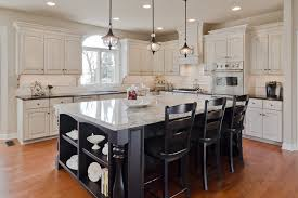 classic vintage pendant lights over black painted wooden kitchen table with white marble granite countertop and