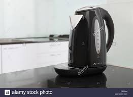 office work surfaces. black kettle in kitchen appliance on work surface office tea coffee time modern and bright surfaces
