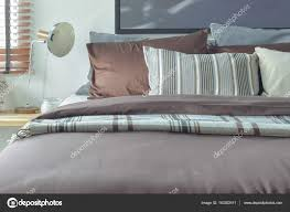 brown and gray color scheme bedding with reading lamp photo by worldwide stock