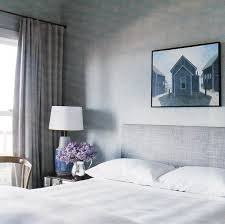 chic gray bedroom gray walls paint color upholstered linen gray headboard crisp white hotel bedding silver pitcher vase gray blue ceramic lamp bedroom gray walls
