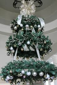 a chandelier made of faux evergreen wreaths and silver and gold ornaments