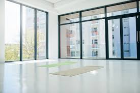 contemporary yoga studio design with white floor walls and ceiling juxtaposed with black framed floor