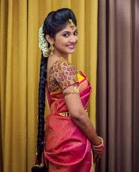 traditional southern indian bride wearing bridal silk saree jewellery and hairstyle braid with fresh flowers