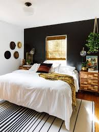 a boho and rustic space with a black headboard wall is balanced with warm colored