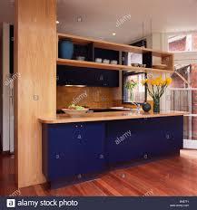 Modern Kitchen Shelving Pale Wood Worktops On Dark Blue Units In Modern Kitchen With