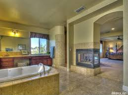 Contemporary master bathroom with fireplace and marble tiles.Source: Zillow  Digs