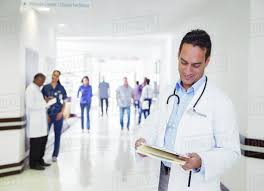 Doctor Reading Chart Doctor Reading Medical Chart In Hospital Hallway Stock Photo