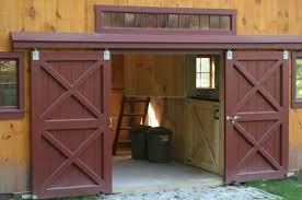 sliding wooden garage doors sit open and have been painted a deep maroon color