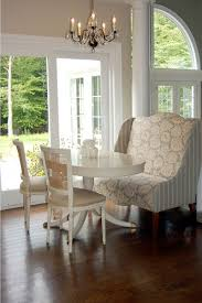 dining rooms wing chair breakfast room wingback settee white pedestal table and crystal chandelier