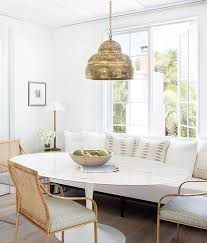 breakfast nook featuring white furniture straw accents gold pendant lighting and plenty of natural light olivia o bryan interiors