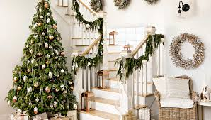 Stairway with decorated garland on banister, wreaths on the walls, a  lighted, decorated