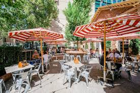 an outdoor dining area with large umbrellas and outdoor furniture