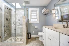 pale blue and beige bathroom with tub converted to a curbed walk in shower