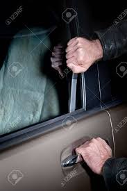 A Car Thief Uses A Slim Jim Tool To Pop The Lock On A Car Door
