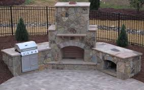 stone fireplace with a grill and wood box