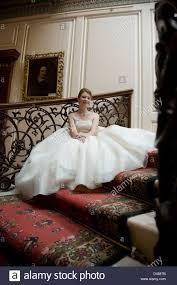 Machen sie ihre hochzeit zur traumhochzeit! Braut In Voll Mit Rockchen Creme Tragerlosen Brautkleid Auf Kunstvolle Innere Treppe Sitzend Stockfotografie Alamy