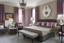 Purple and gray bedroom features walls painted warm gray lined with a dark  gray bed dressed