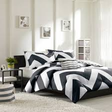 good looking black and white comforter on wooden bed frame which is installed in modern bedroom completed with minimalist storage bedroom furniture black and white