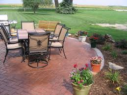 outdoor flooring over concrete with beautiful small flowers in vases surrounded by vast green meadow