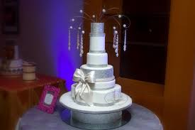 multi tiered white cake with bow and decoration at top