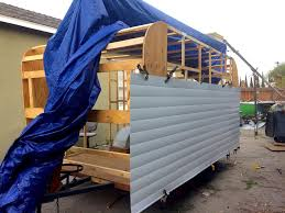 attaching the bottom piece of siding to the frame excuse the giant blue tarp in