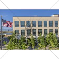 American Flag Next To Office Building And Trees Gl Stock Images