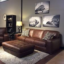 Family room with warm gray walls, black and white art, brown leather  furniture,