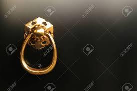 gold ring pull handle on black door stock photo 31728509