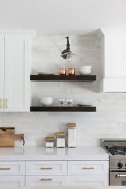 calacatta marble kitchen waterfall: floating shelves mounted on the calcutta marble tile provide a stylish spot to display copper and
