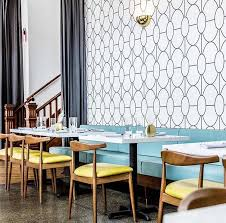 pretty turquoise banquette graphic wallpaper yellow mid century modern dining chairs retro vibe dining room inspiration brittini mehlhoff ig