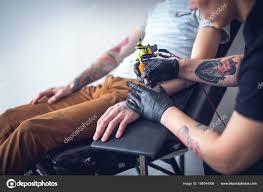 Master Tattoo Artist In Gloves Makes Tattoo Stock Photo