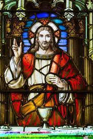 Close up of stain glass window with Jesus Christ at a table with chalice  and holding bread; Calgary, Alberta, Canada - PacificStock