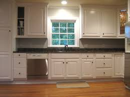 simplistic galley kitchen decors with gloss paint cabinets white and black granite countertops as well as brown oak laminate wood floor installations