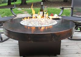 Fire Pit, Hammered Copper Fire Pit Round Black Varnished Wooden Table  Transparent Glass Bottle Chair
