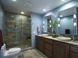 recessed lighting over bathroom vanity with sliding glass door and drawer using natural stone tiles