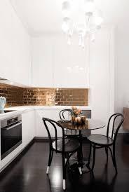 black vinyl floor balck dining set circular dining table black stained chair white wooden l shape kitchen cabinet golden brick pattern backsplash oven range