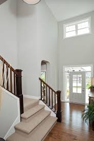 Wall color is Repose Gray Sherwin Williams. 2 storey entryway foyer and  stairwell with beige carpet on stairs.