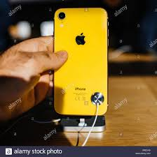 STRASBOURG, FRANCE - OCT 26, 2018: Customer POV holding new yellow iPhone XR  smartphone rear view in Apple Store Computers during the launch day  admiring the yellow glass with logo customers background