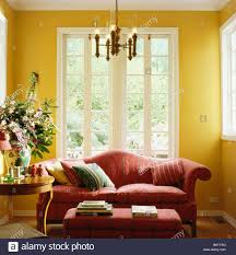 Living Room With Red Sofa Red Sofa In Front Of French Windows In Yellow Living Room With