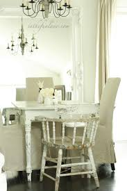 white cottage dining room with white baroque floor mirror reflecting view of whitewashed farmhouse dining table