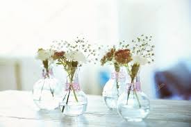 mini glass vases with flowers on table stock photo