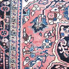 large pink rug with medallion and blue yellow detail for