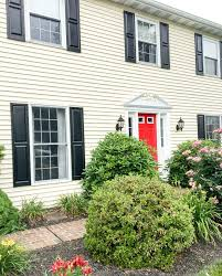 yellow house with black shutters and red door