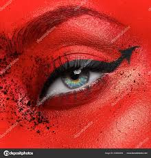 macro and close up creative make up theme beautiful female eye with red skin a look of the devil photo by
