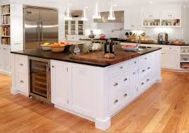 absolute black granite pencil countertop big wooden cutting board white stained kitchen island fridge built in with clear glass door chrome contemporary cup