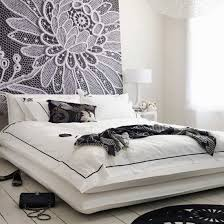 white bed black furniture. stunning feature wall with a simple double bed and white floorboards black furniture
