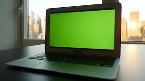 laptop office desk. laptop computer with isolated green screen background modern city office desk view working at