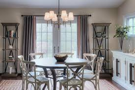dark stained round dining table with white x back chairs